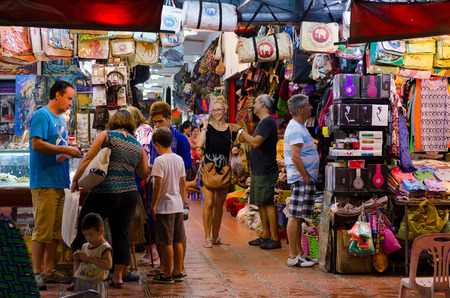 SIEM REAP, CAMBODIA - JUNE 21, 2014: Unidentified tourists shop at the night market of Siem Reap. The city serves as a gateway to the world famous Angkor temples and is a major tourist hub. Editorial