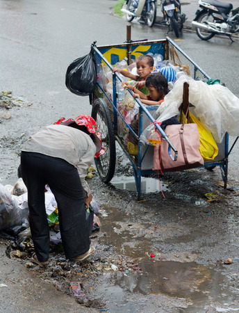 supposedly: PHNOM PENH, CAMBODIA - JULY 3, 2014: An unidentified senior dustwoman picks recyclable trash by her cart where two children sit, supposedly her grandchildren. In Khmer family everyone must earn.
