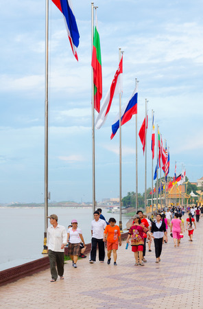 tonle sap: PHNOM PENH, CAMBODIA - JULY 3, 2014: Unidentified Asian people walk along Tonle Sap River in the downtown near the Royal Palace.