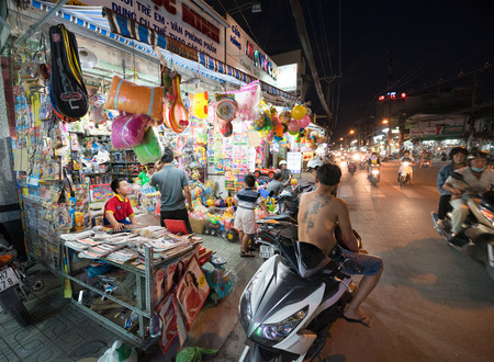 evening newspaper: HO CHI MINH, VIETNAM - DECEMBER 28, 2014: Unidentified people sell and buy things in the evening in Le Van Tho street. Many shops and stores open at sunset - about 5 or 6 p.m. Editorial