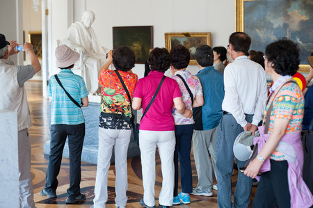 million: ST. PETERSBURG - JUNE 30, 2011: Unidentified Asian tourists photograph the statue Voltaire by Houdon Jean Antoine at the Hermitage. Over 3 million people visit the museum every year.