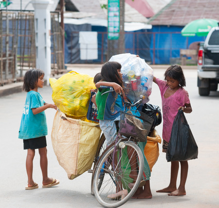 28: SIEM REAP, CAMBODIA - JUNE 28, 2014: Four local unidentified girls of school age arrange large bags with different kinds of trash on a bicycle. In Khmer family every member must earn money.