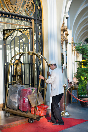 HO CHI MINH, VIETNAM - JAN 15, 2015: An unidentified porter pulls a cart with suitcases into the entrance door of the hotel Majestic. It is a luxury hotel built in 1925 on the Saigon River bank. Editorial
