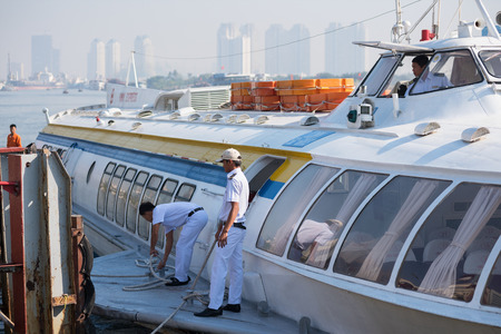mooring: HO CHI MINH, VIETNAM - JANUARY 15, 2015: A hydrofoil of the Vina Express transportation company is mooring at the Saigon ferry station to take passengers to Vungtau. Editorial
