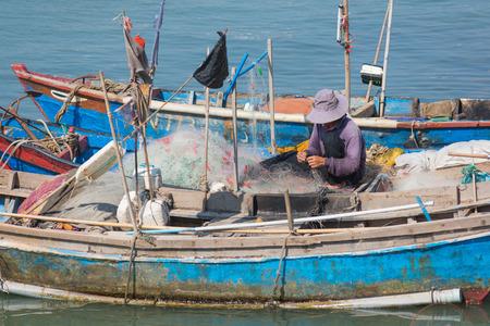 untangle: Vietnamese fisher untangles nets sitting in boat