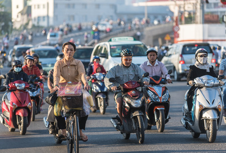 indochina: HO CHI MINH, VIETNAM - JANUARY 15, 2015: Unidentified people move by motorcycles and cars early in the morning in downtown. Motorcycle is the most popular transport in Indochina. Editorial