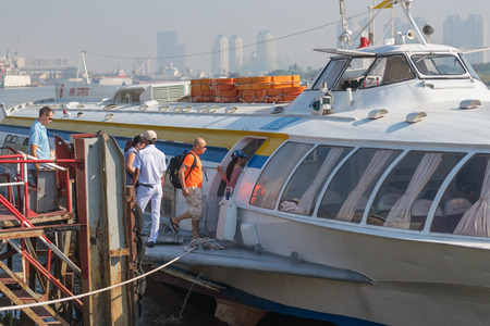 mooring: HOCHIMINH, VIETNAM - JANUARY 15, 2015: A hydrofoil of the Vina Express transportation company moored at the city ferry station takes passengers on the board.