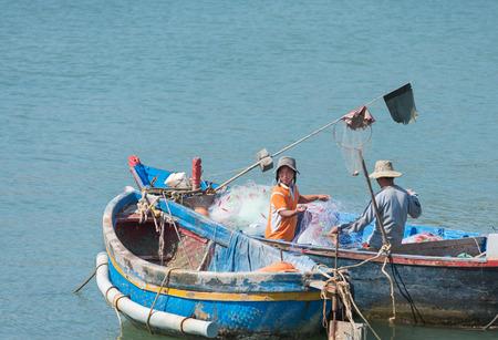 untangle: two Vietnamese fishers untangle nets sitting in boat