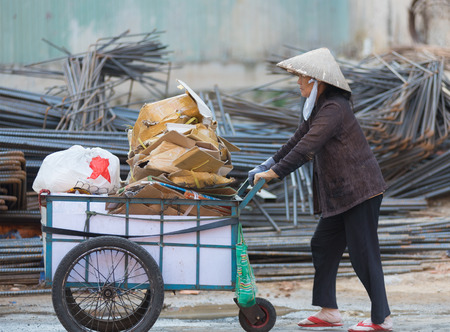 sorted: HO CHI MINH, VIETNAM - JAN 15, 2015: An unidentified senior dustwoman rolls a cart with different kinds of sorted waste for recycling. Waste selling for recycling is popular business in Vietnam.