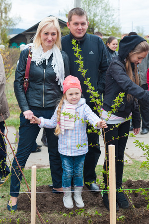 nursling: ULAN-UDE, RUSSIA - MAY 20, 2011: Unidentified parents and their daughter plant young trees near the City Palace of Childrens Arts. Children who now attend the palace and its graduates work together.