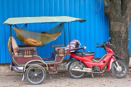 a Cambodian driver sleeps in hammock in his tuktuk