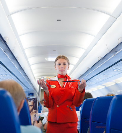 モスクワ - 2011 年 5 月 28 日: 航空のスチュワーデス アエロフロート ユリア ボード上の安全ベルトを使用する方法を示します。アエロフロートは主要