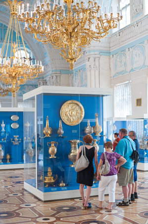 ST. PETERSBURG - JUNE 30, 2011: Unidentified people walk and watch gold vessels at one of the Hermitage halls. Over 3 million people visit the museum every year.
