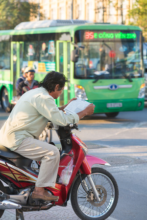 indochina: HO CHI MINH, VIETNAM - JANUARY 15, 2015: An unidentified taxi motorcyclist (xe om) reads a newspaper waiting for clients early in the morning. Motorcycle is the most popular transport in Indochina.