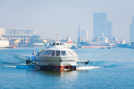 land transportation: HO CHI MINH, VIETNAM - JANUARY 15, 2015: A hydrofoil of the Vina Express transportation company is going to land at the Saigon ferry station to take passengers to Vungtau. Editorial