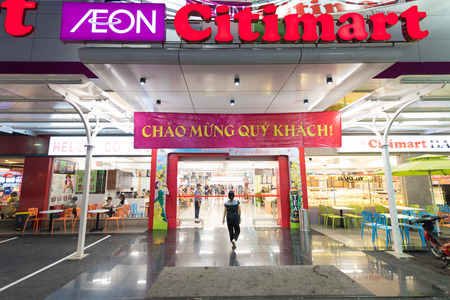 retailing: HO CHI MINH, VIETNAM - JAN 13, 2015: An unidentified woman enters a Citimart supermarket. Supermarkets are uncommon in Vietnam, open air markets and small businesses are the main players in retailing.