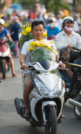 descend: HOCHIMINH, VIETNAM - FEB 17, 2015: An unidentified motorcyclist drives many yellow flowers on Tet Eve. Yellow means noble roots of Vietnamese (as legends say they descend from a dragon and a fairy).