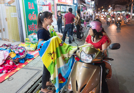 retailing: HO CHI MINH, VIETNAM - JAN 1, 2015: An unidentified woman sells a blanket to women motorcyclists. Open air markets and small businesses are main players in retailing in Vietnam. Editorial