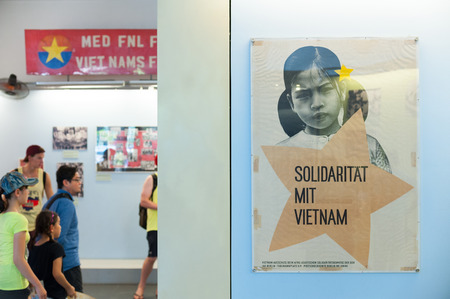 remnants: HO CHI MINH, VIETNAM - AUGUST 12, 2014: Unidentified tourists watch photographs at the War Remnants Museum. It primarily contains exhibits relating to the American phase of the Vietnam War. Editorial