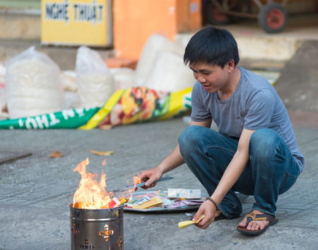 idolatry: HO CHI MINH, VIETNAM - FEB 17, 2015: An unidentified man burns votive offerings by his house on Tet Eve. Many Vietnamese practice the custom of burning votive objects for religious purposes mainly.