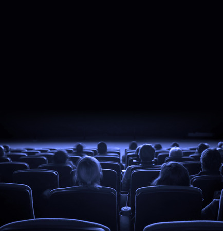 blue wall: viewers watch motion picture at movie theatre, long exposure, blue toning