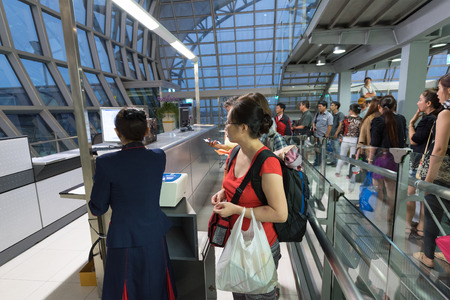 airport check in counter: BANGKOK - MARCH 18; 2015: Unidentified air passengers register to board the flight of the Vietjet Air company. The Bangkok International Airport Suvarnabhumi is the sixth busiest airport in Asia.