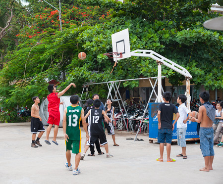play popular: NHA TRANG, VIETNAM - AUG 5, 2014: Unidentified teenagers play basketball in a yard in the downtown. The city is a very popular fast developing sea resort.