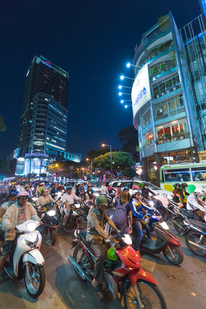 indochina: HO CHI MINH, VIETNAM - JANUARY 15, 2015: Unidentified people move by motorcycles and cars early in the evening in downtown. Motorcycle is the most popular transport in Indochina.