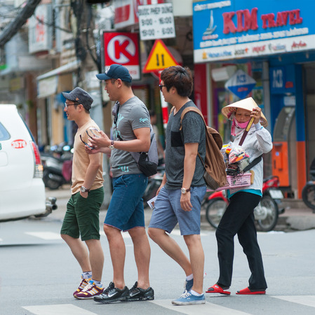 trifles: HO CHI MINH, VIETNAM - JULY 6, 2014: Unidentified Asian tourists cross the road followed by a street pedlar woman. Street pedlars in Pham Ngu Lao usually sell small souvenirs and trifles.