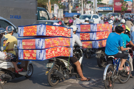 HO CHI MINH, VIETNAM - MARCH 28, 2015: Unidentified men drive new matrasses on their motorcycles back seat. For foreigner surprise locals manage to take any load on their tiny motorcycles.