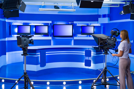 teleoperator: woman cameraman works at empty blue TV studio