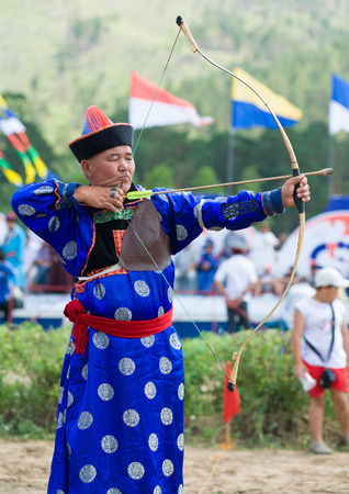 naadan: ULAN-UDE, RUSSIA - JULY 17, 2010: An unidentified man is ready to shoot during Mongolian archery competition. The 4th General Session of the World Mongolians Convention took place in Buryatia.