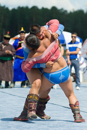 naadan: ULAN-UDE, RUSSIA - JULY 17, 2010: Two unidentified men compete in Mongolian national wrestling in heavy weight during the 4th General Session of the World Mongolians Convention.