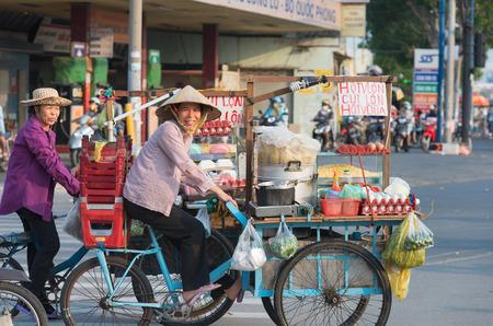호치민 - 2015 년 4 월 19 일 : 두 명의 정체 불명의 지역 여성 요리사가 Truong Chinh Street을 따라 자신의 자전거 카트를 업무로 옮깁니다. 그들의 사업은 거 에디토리얼
