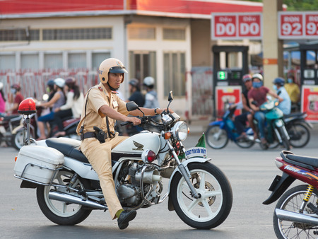 HO CHI MINH, VIETNAM - APRIL 19, 2015: An unidentified traffic policeman inspects the road Truong Chinh Street during rush hours. The main means of transport in Vietnam is motorcycle.
