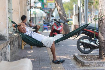 siesta: VUNG TAU, VIETNAM - JAN 15, 2015: An unidentified man having noon rest in a hammock smiles into camera. Midday sleep is a must in Vietnam. Editorial