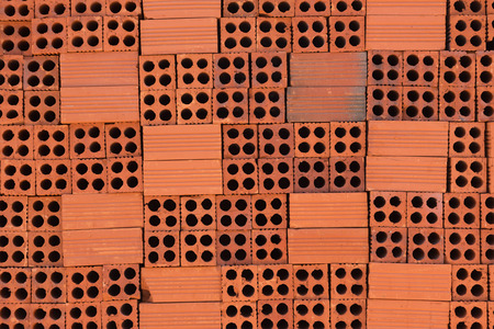 holed: wall of piled red perforated bricks as background Stock Photo