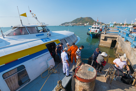 mooring: VUNGTAU, VIETNAM - JANUARY 15, 2015: A hydrofoil of the Vina Express transportation company moored at the Vungtau ferry station takes passengers off the board.