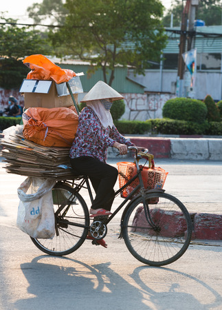 sorted: HO CHI MINH, VIETNAM - APRIL 19, 2015: An unidentified dustwoman rides a bicycle carrying sorted waste, cardboard, for recycling. Waste selling for recycling is popular business in Vietnam.