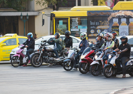 BANGKOK - MARCH 20, 2015: Unidentified motorcyclists and vehicles stand at a traffic light in Samsen Road. Over 30 per cent of private vehicles in Bangkok are motorcycles.