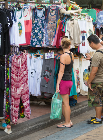travelling salesman: BANGKOK - MARCH 9, 2015: An unidentified woman tourist chooses a tshirt to buy at a street shop in Khao San Road. It is lined up with hotels, shops, massage salons, bars and restaurants. Editorial