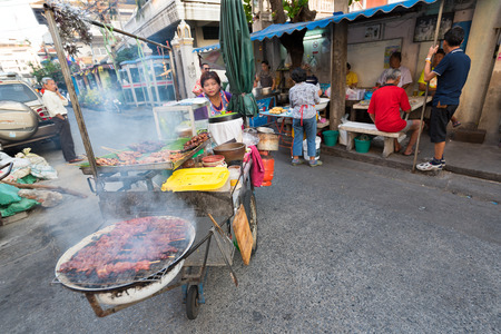 BANGKOK - MARCH 9, 2015: An unidentified local woman pushes her cart with bbq being grilled in the Khao San Road area, the center of the backpackers universe.