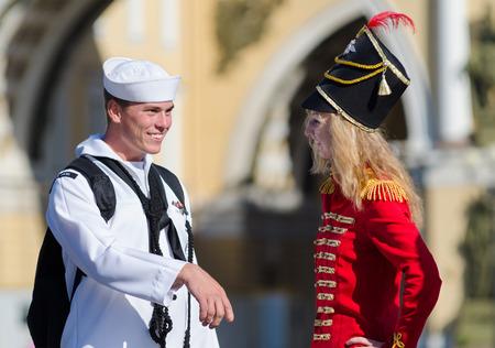 palacio ruso: ST PETERSBURG - 29 de junio de 2011: Un marinero estadounidense no identificado hace que el conocimiento de una joven rusa vestido como un soldado ruso del siglo 19 en la Plaza del Palacio. La ciudad es destino turístico número uno en Rusia. Editorial