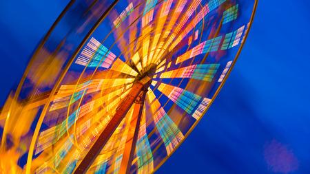 merrymaking: turning illuminated ferris wheel shot at long exposure Stock Photo
