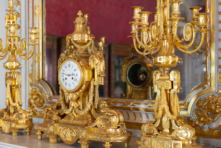 hermitage: ST PETERSBURG - JUNE 30, 2011: A golden fireplace clock with two candelabra in one of halls of the Hermitage Museum. Today the collection of the museum contains about 3 million items.
