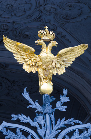 double headed: ST. PETERSBURG - JUNE 30, 2011: One of three golden double headed eagles at forged gate at Southern facade of the Winter Palace. From 1732 to 1917 it was the official residence of Russian monarchs.