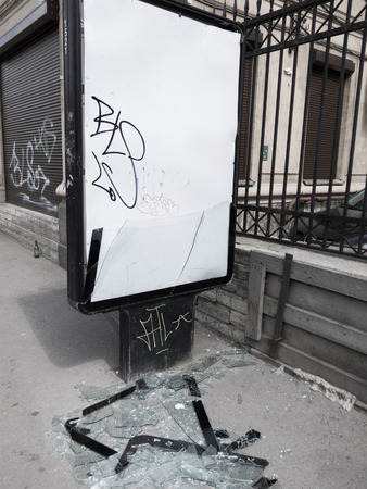smithereens: vandalism in the street - an advertisement stand with broken glass