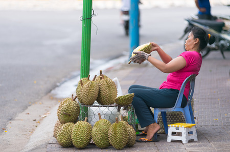 regarded: VUNG TAU VIETNAM JUNE October 2015: An unidentified woman peels and sells durian fruit. Regarded by locals as the Editorial