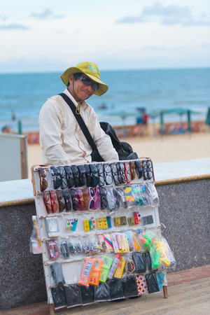 trifles: VUNG TAU, VIETNAM - JUNE 10, 2015: An unidentified local man pedlar selling sunglasses at the beach looks into camera smiling. Vung Tau is a sea resort in the southern Vietnam. Editorial