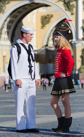 palacio ruso: ST. PETERSBURG - 29 de junio de 2011: Un marinero estadounidense no identificado conoce a una joven rusa vestido como un soldado ruso del siglo 19 en la Plaza del Palacio. Es la principal atracción turística de la ciudad.
